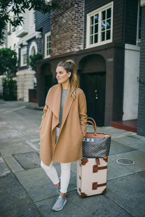 Woman in camel coat and white pants next to luggage