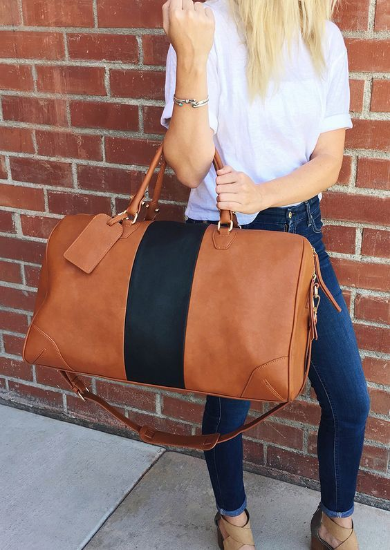 Woman in front of brick wall holding big travel bag