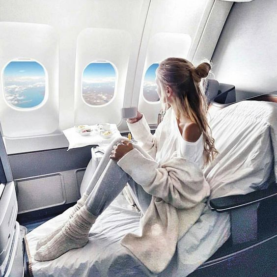 Woman sitting in business class on plane with white sheets
