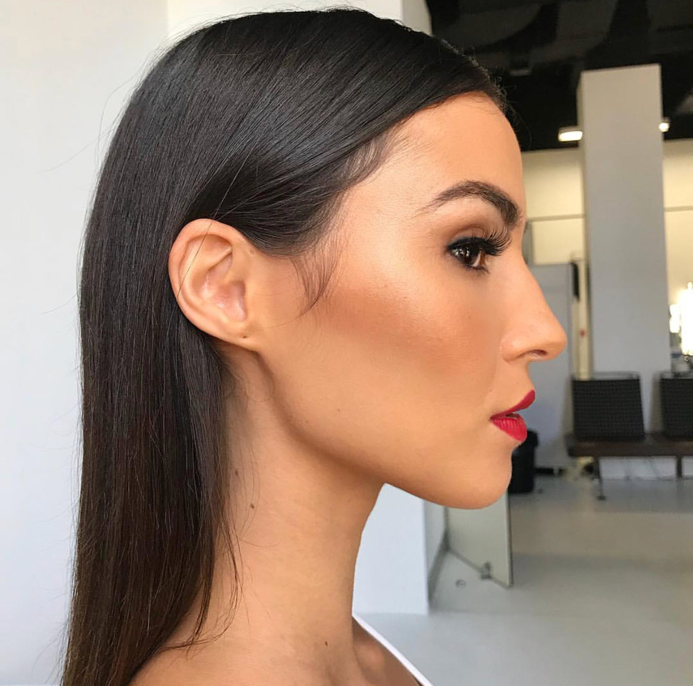 Side profile shot of brunette models face with hair pulled behind ear, wearing red lipstick and fake eyelashes