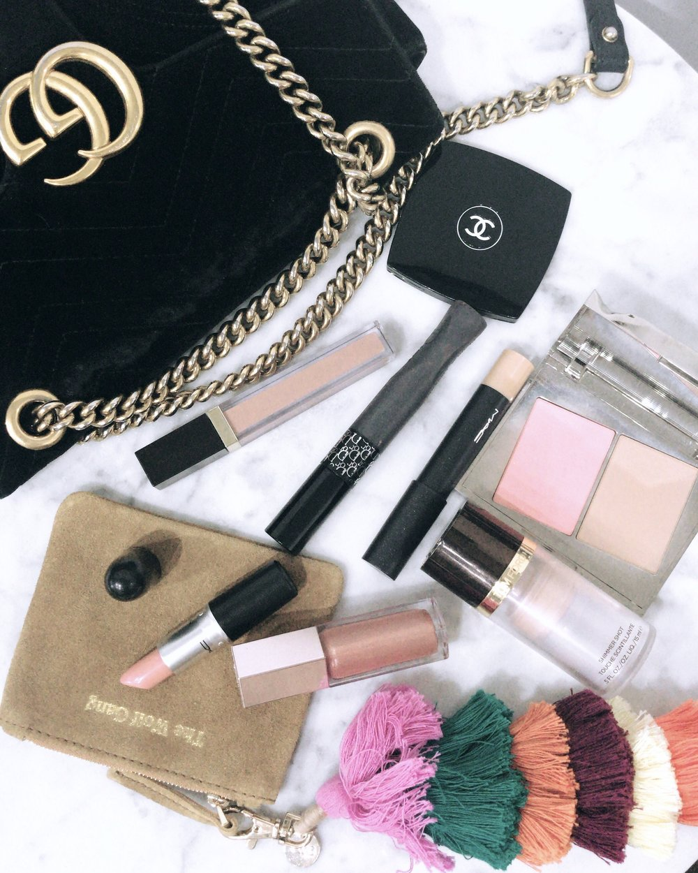 A range of make up products and fashion accessories laid out against a white background