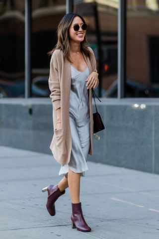 Woman in long beige cardigan and brown boots