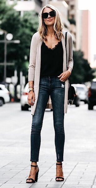 Woman in long beige cardigan and blue jeans
