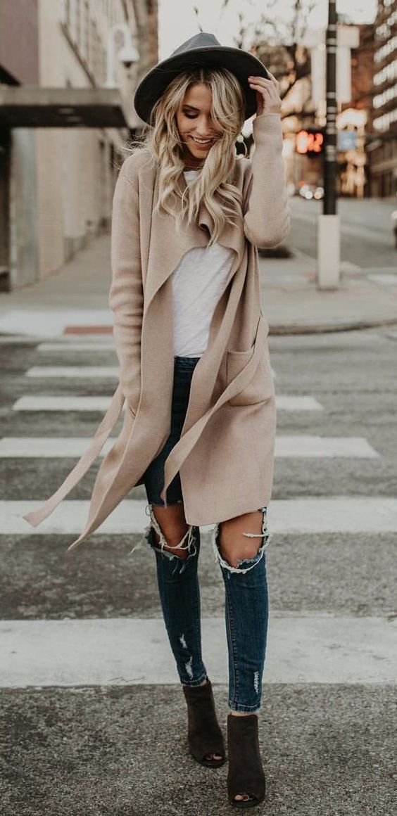 Blonde woman in long boots and beige cardigan
