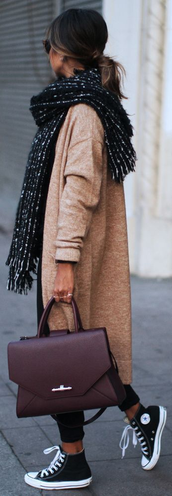 Woman in black converse and beige cardigan