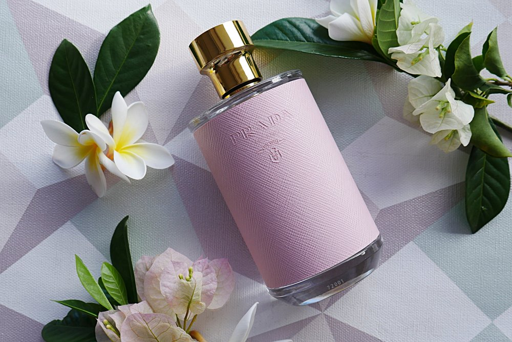 Prada perfume in pink bottle laid out on a geometrical background surrounded by white flowers