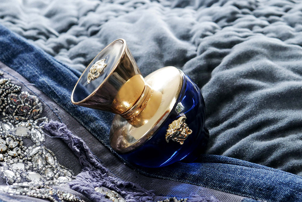 Versace perfume in blue and gold bottle on blue background