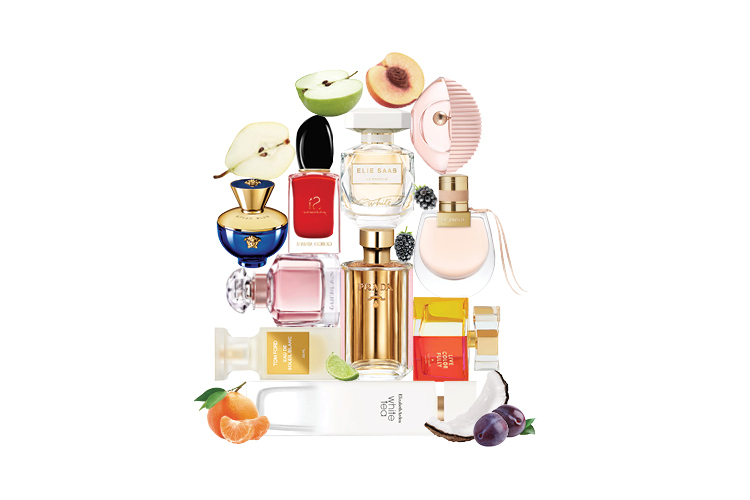 A range of different fragrances arranged in a dome shape against a white background surrounded by fruits