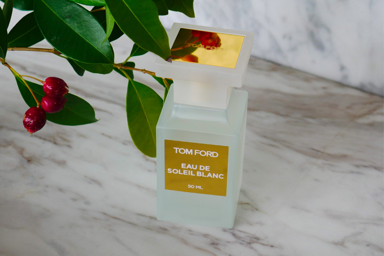 Matte white rectangular frangrance bottle with a matte white cap and on top of the cap a square gold label with Tom Ford etched into the gold. Label on the bottle is gold with white type. Fragrance is on a white marble table and a cherry branch is lightly touching the bottle from the top left.