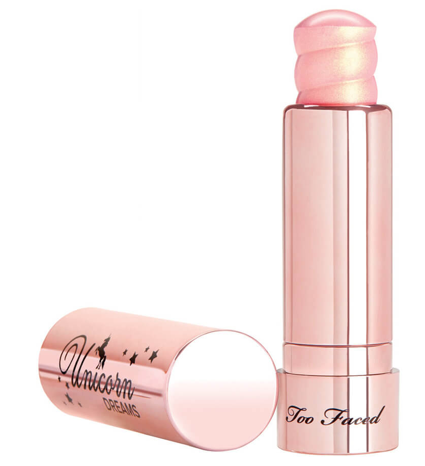 Too Faced Unicorn Horn Highlighting Stick with lid laying next to pink bottle