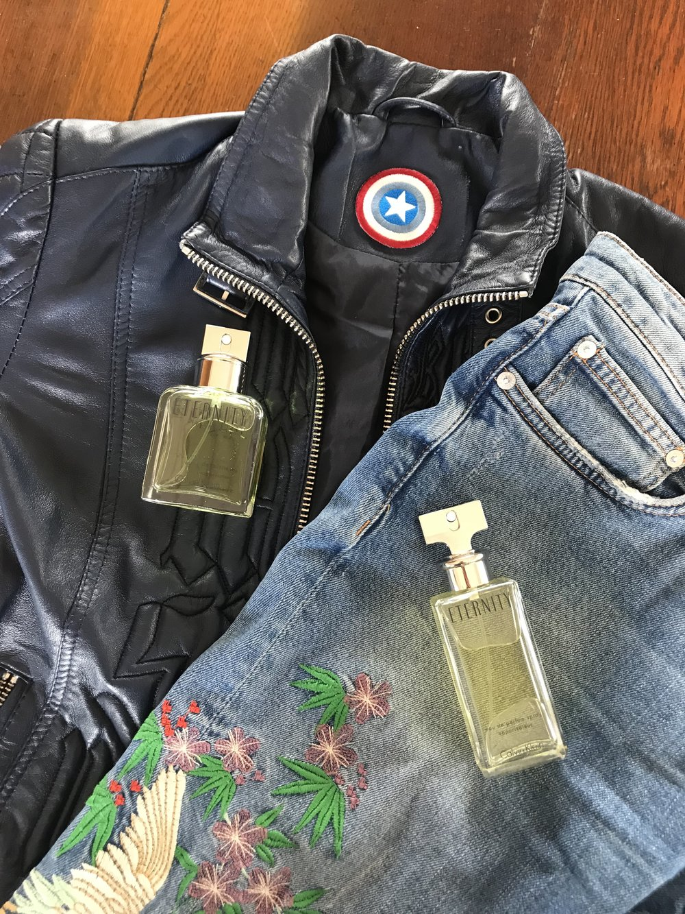 Eternity gold coloured fragrance bottle on a pair of blue jeans with a floral print on them. Black Leather jacket underneath the blue jeans with the eternity gold coloured fragrance on the jacket with a hardwood floor showing