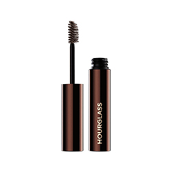 HOURGLASS  Arch Brow Volumizing Fiber Gel with lid standing upright next to brown bottle
