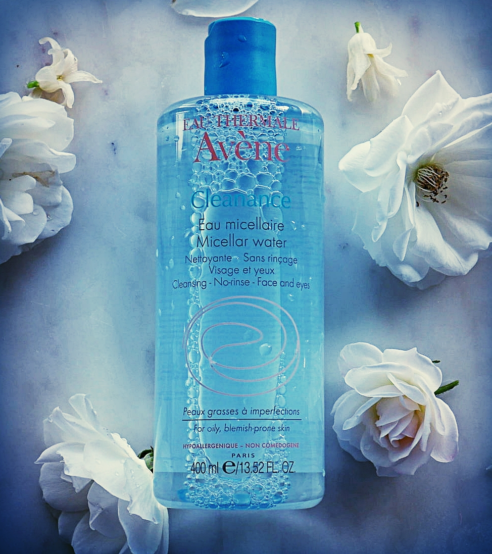Eau therme avene cleance miceller water in blue bottle laid out on a blue background surrounded by white flowers