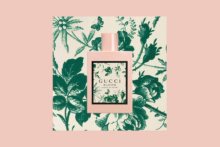 Salmon coloured background with a square of green flora in a biege background within it. The bottle is in the middle of this square in a salmon colour with a square of green flora in a beidge background as the label of the fragrance