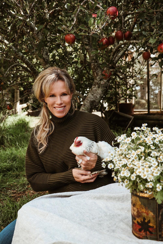 Food stylist Fiona Hugues in her garden under the apple trees