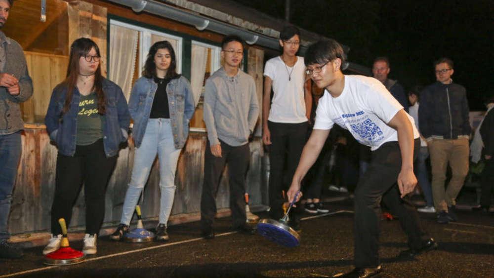 Leicht skeptisch schauen die Asiaten drein, die sich im Stockschießen versuchen. So oft werden sie noch keinen Eisstock in der Hand gehabt haben. ©joho