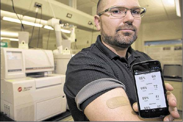Joshua Hagen shows the bandage-sized sensor that he and other scientists at the 711th Human Performance Wing developed at Wright-Patterson Air Force Base to monitor the perspiration of soldiers and athletes.TY GREENLEES / Dayton Daily News STAFF