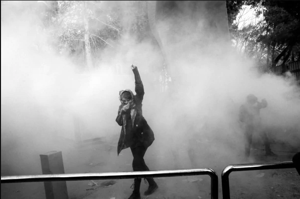 A protester uses her scarf for cover against tear gas