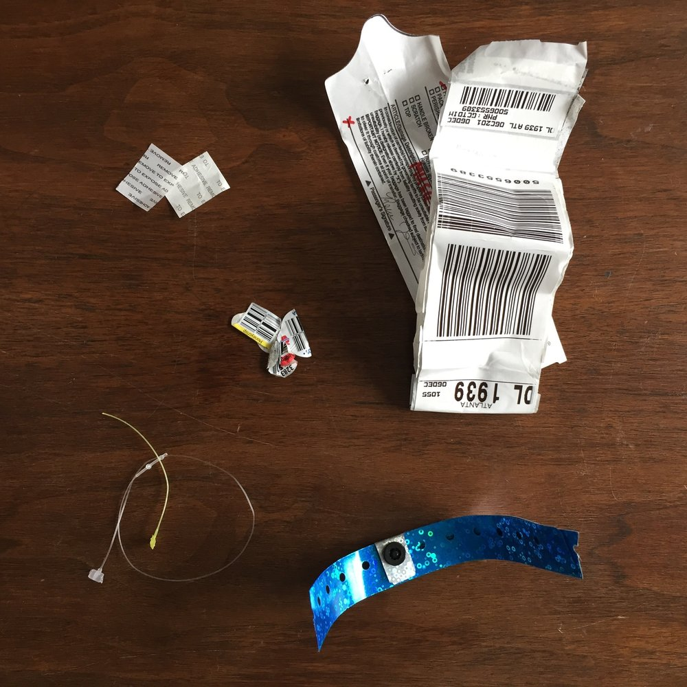 Clockwise from upper left: sticker backing from a wristband, checked bag stickers (had to check my keyboard), plastic produce stickers, plastic tags from a thrift-store purchase, non-recyclable wrist band.