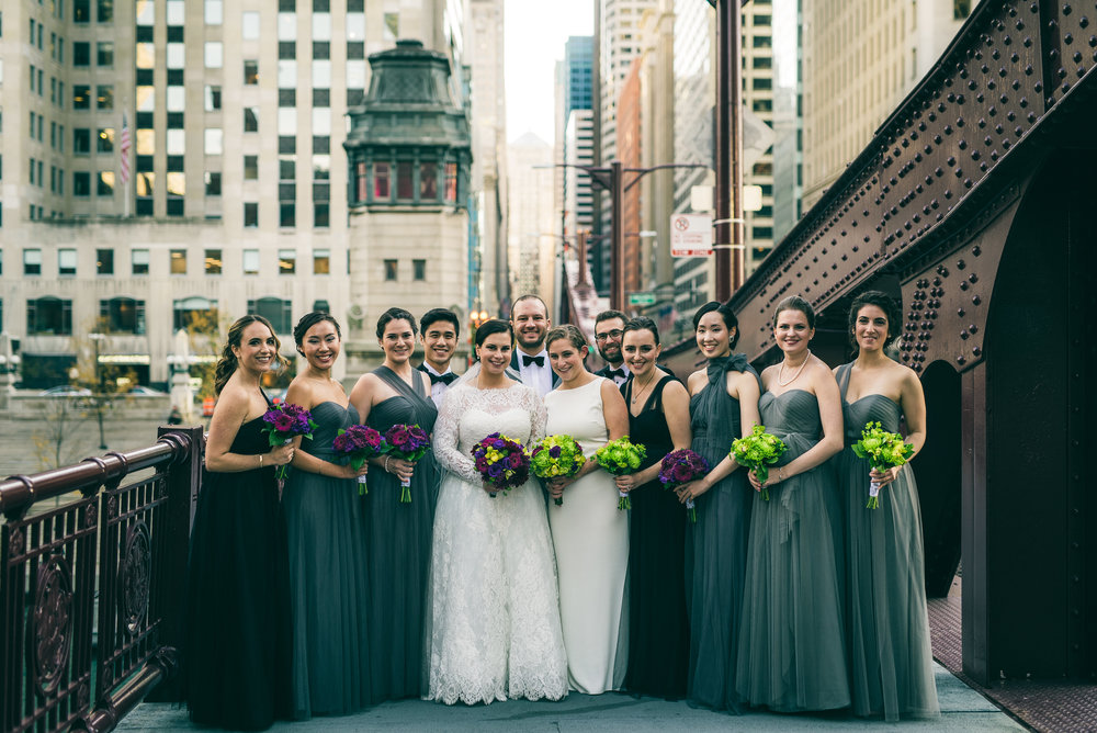 Bridal party and brides in same sex wedding, downtown Chicago. Green and purple wedding colors, sage green bridesmaids dresses.