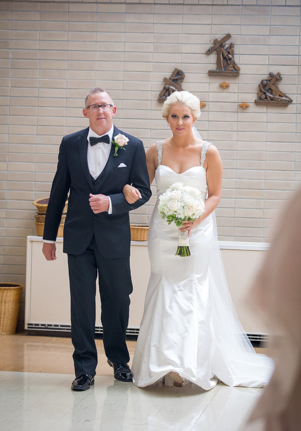 Bride walking down the aisle with Father for church wedding