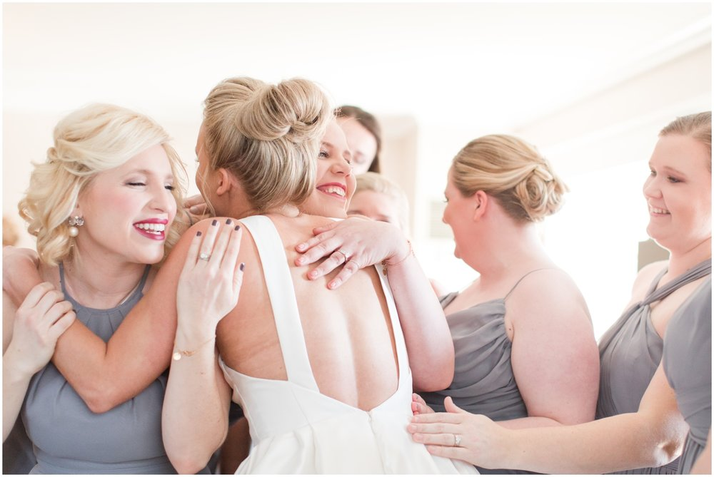 bridesmaids hugging the bride