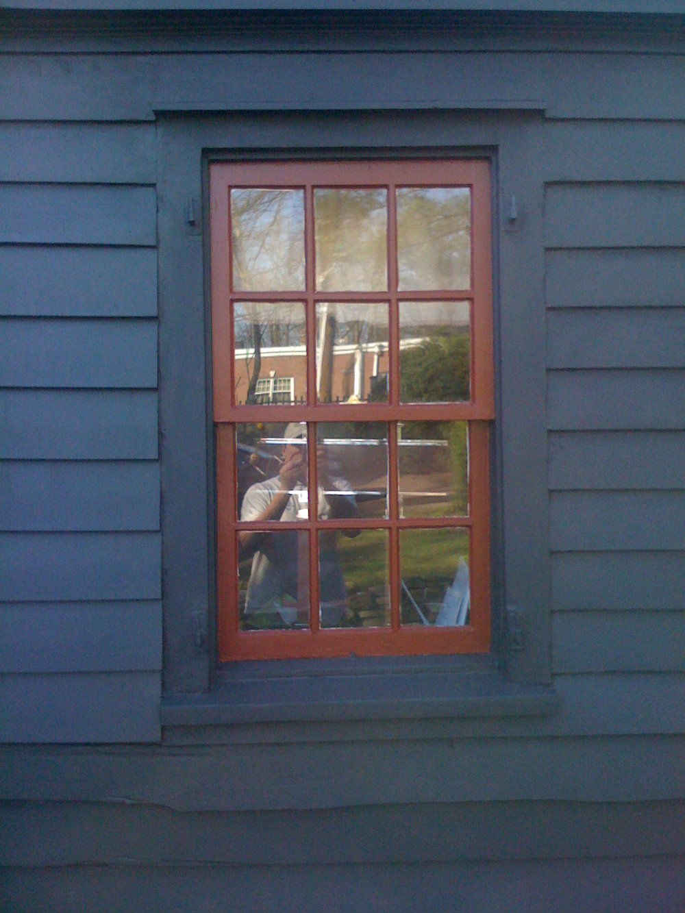 blue wood siding with red windows and sashes on exterior wood
