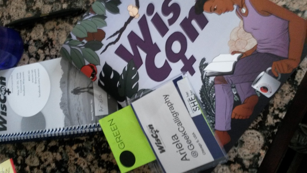 Ariela's name badge and program books from WisCon40.