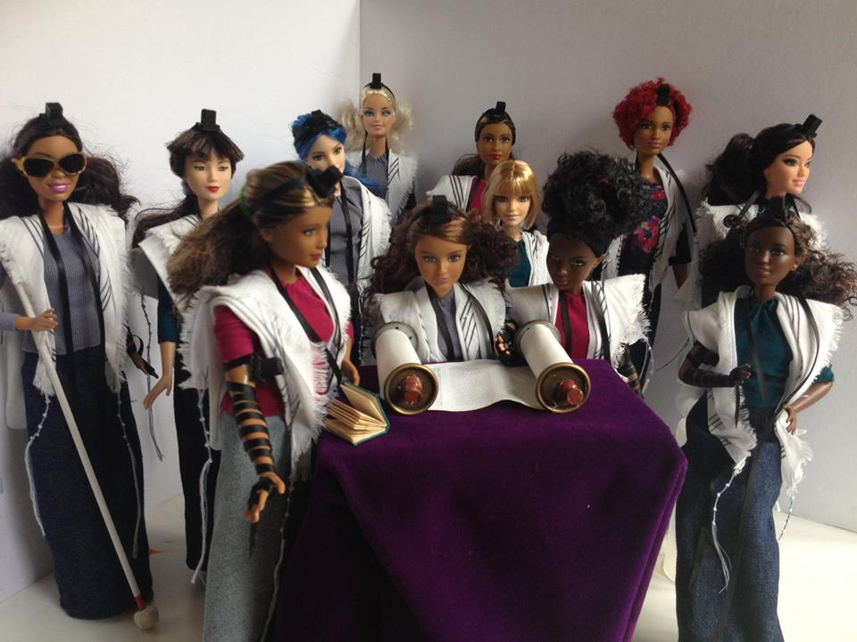"Intersectional Barbie Dream Minyan points to the Jews who are still excluded, not intentionally but effectively, from our communities. Barbies of many different ethnicities, wearing tallit and tefillin, are having a Torah reading. All the Barbies are wearing long denim skirts and three-quarter length sleeves. That's how I do Tefillin Barbies. They're also all wearing tallitot. One of the Barbies isn't wearing tefillin, and she's wearing a jaw-length sheitl. Perhaps she put her tefillin on before she left home, or perhaps she just doesn't do tefillin at this point in her life. Some of the Barbies are Black, some of them are Brown. Some of them are tan, some of them are pale. Maybe some of them are Sephardic and some are Maghrebi and one is an adult convert and one was adopted and converted as a child. One of them has blue hair. One of them has red hair, and one of them has red highlights. Nobody in this minyan ever says ""But where are you *really* from?"" or ""But surely you weren't born Jewish."" Some of them are what Mattel calls ""curvy."" Some of them are short. One of the Barbies has a white cane and dark glasses. You can't see her Braille siddur in the picture. She doesn't need it right now anyway because they're about to do hagbah. Another of the Barbies is sitting down because she has mobility issues and chronic pain. Another one has depression, and another one has hearing issues, but you can't tell which ones. Two of the Barbies are married to each other. One of the Barbies is trans. One of the Barbies couldn't afford a set of tefillin for herself, and the community helped out. Some of these Barbies didn't go to college, or were the first in their families to go to college. One of them works in construction. All the Barbies are deeply conscious that they're all awfully young. The artist has not the skill to repaint Barbie faces to make them look older, nor to make their hair grey. In principle, Kens are welcome in this minyan, but today they're outside fixing breakfast, which is why you can't see them."