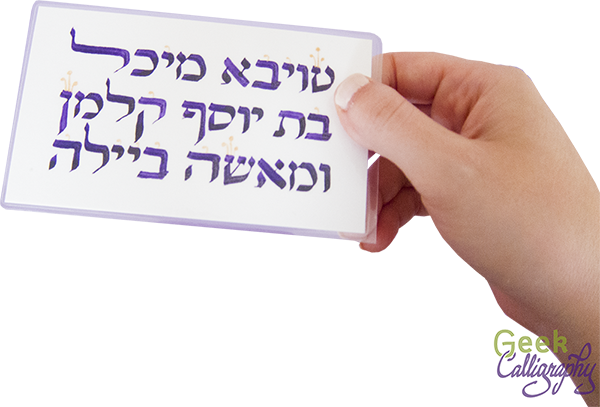 Image shows Ariela's hand holding Terri's name card. Letters are in purple (of course) with gold  tagin /crowns.