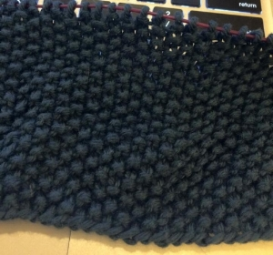 Image shows one of the plain squares in progress. It is a dark blue yarn, knit in seed stitch.