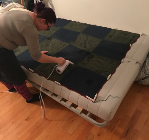 Image shows me holding a very small steamer over the afghan all pinned out on our IKEA sofa bed in the bed position. This is what one kind of blocking looks like.