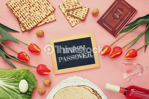 "Image shows a wood framed slate with ""HAPPY PASSOVER"" written on it in stylized chalk lettering. Surrounding the frame clockwise from noon are: pieces of square machine made maztah, unshelled walnuts, a red-brown  haggadah , red tulips with yellow stripes, a wine glass on its side with a splash of wine still left, a bottle of pink wine on its side, a stack of three round hand made matzahs on a white cloth, more unshelled walnuts, a leaf of lettuce with an egg on it, and more tulips."