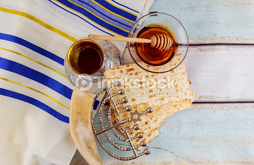Image shows a  tallit  with blue and gold stripes over white painted wooden slats. Positioned over the  tallit  are (clockwise from top): glass bowl with honey and wooden dipper, two broken sheets of square machine made matzah, a  chanukiyah  lying flat on its side, a  shofar , and a silver  kiddush  cup partially filled with wine and sitting on a silver coaster.