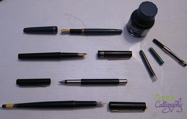 Several uncapped fountain pens with cartridges and a bottle of ink.