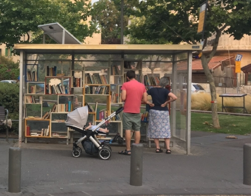 Half of Reading Station/תחנת קריה. This is an old bus stop, repurposed into a free library.  [Image shows a man, woman and stroller in front of a bus shelter filled with bookshelves]