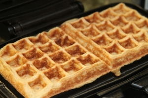 Two square waffles side by side in a waffle iron.
