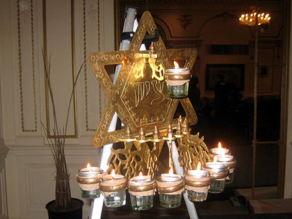 A large, synagogue style Indian  chanukiah . It is formed of a large six pointed star made of brass, with the 8 lights of the holiday in an arc around the bottom and the  shamash  (helper candle) near the center of the star.
