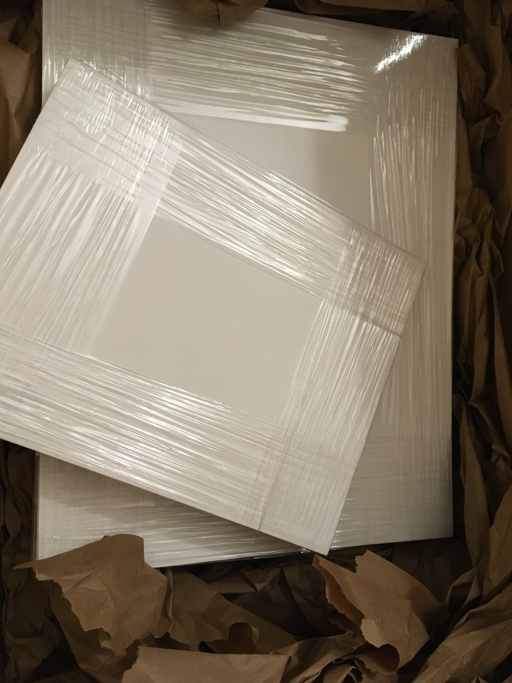Backboards. It turns out that it's cheaper to buy pre-cut matboard for the back of a print than it is to cut them ourselves.  [Image shows stacks of 11x14 and 8x10 backboards plastic wrapped together, surrounded by brown packing paper]