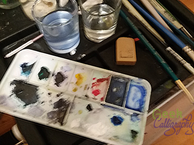 Paint palette with lots of dark blues and greens and purples and greys, some whites, a yellow, and a light blue. Eraser, brushes, and two cups of water in the background.