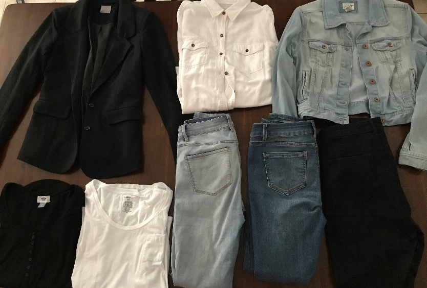 Pictured are a few basic pieces of clothing; including: a blazer, a white and black shirt, a button up shirt and jeans.