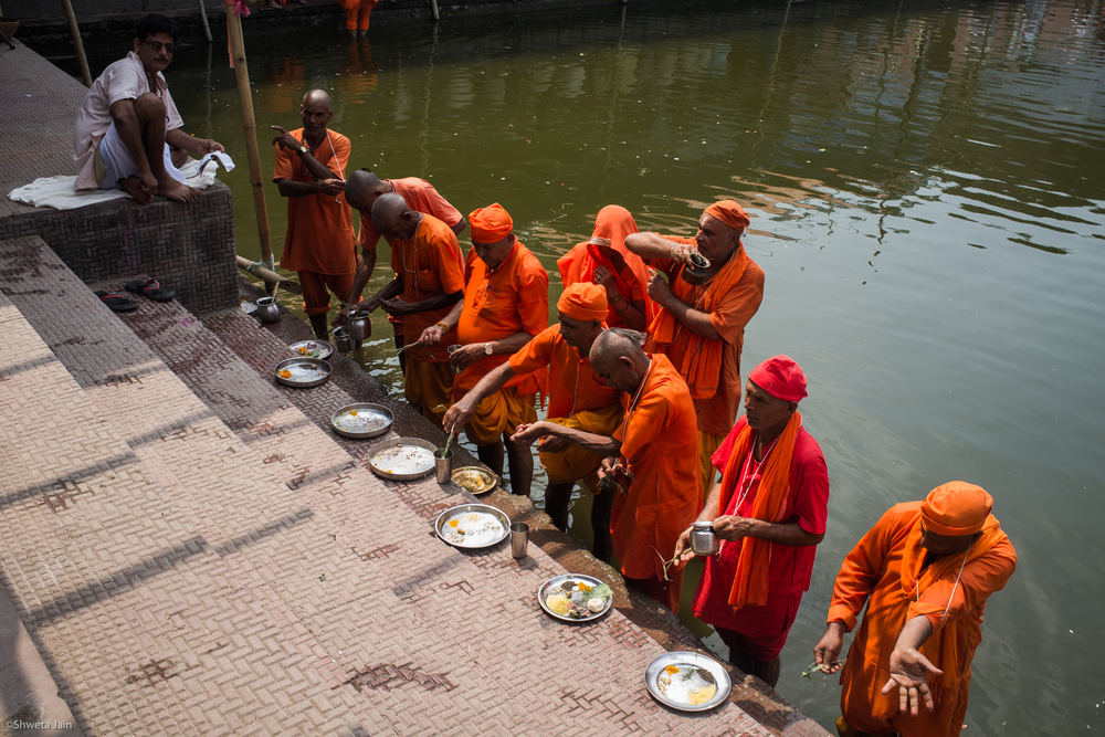 Pilgrims offering water during 'Pind Daan' ritual as the priest chants 'mantras' (prayers) at Baiterni lake. It is essential to perform the ritual at different pious sites. Gaya, Bihar, India. 2015