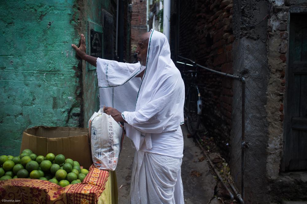 A pilgrim awaits his turn for sweet lemon juice, a common drink consumed during breaks in 'Pind Daan'rituals.Gaya,Bihar, India. 2015