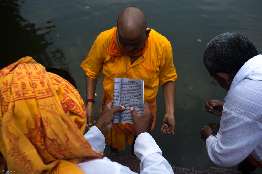All the prayers are read in sanskrit from the ancient Hindu scriptures and the pilgrims have to perform acts as the priest chants prayers. Baiterni Lake, Gaya, Bihar, India 2015