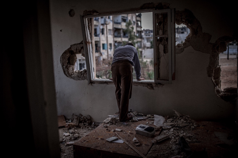 A man visits his damaged home for the last time to pick up his remaining belongings