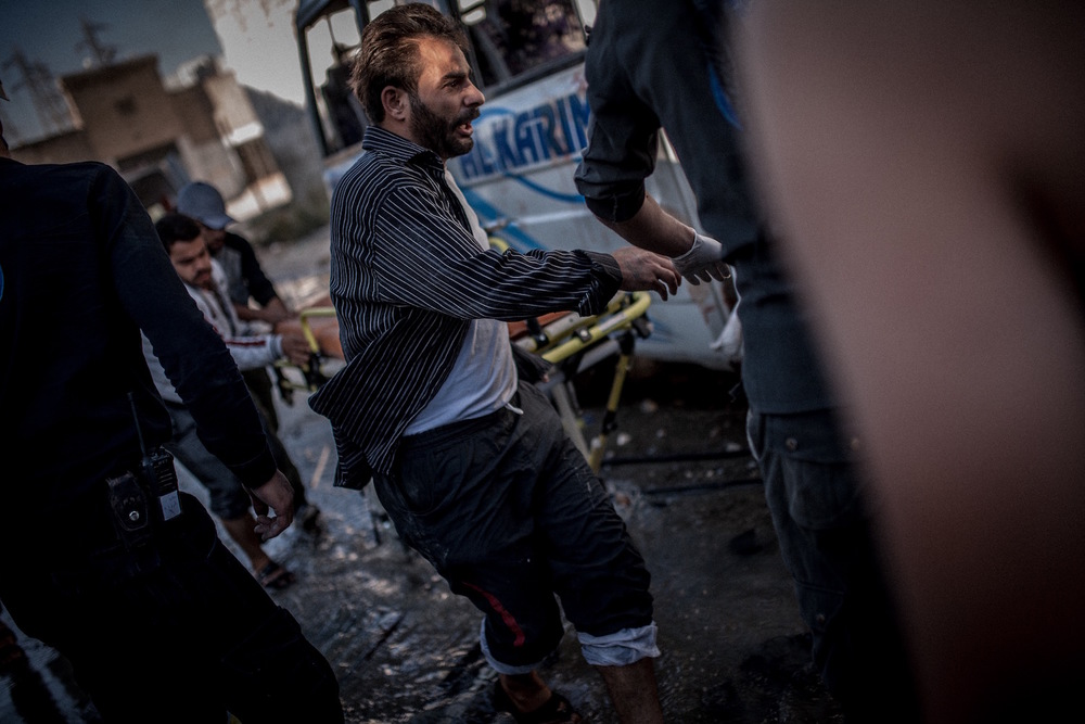 A passerby supports the  Civil Defense Force  to salvage wounded civilians after a barrel bomb attack