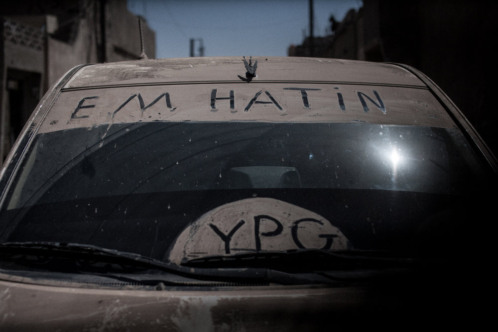 """We are coming"" is written on this windscreen of a YPG car"