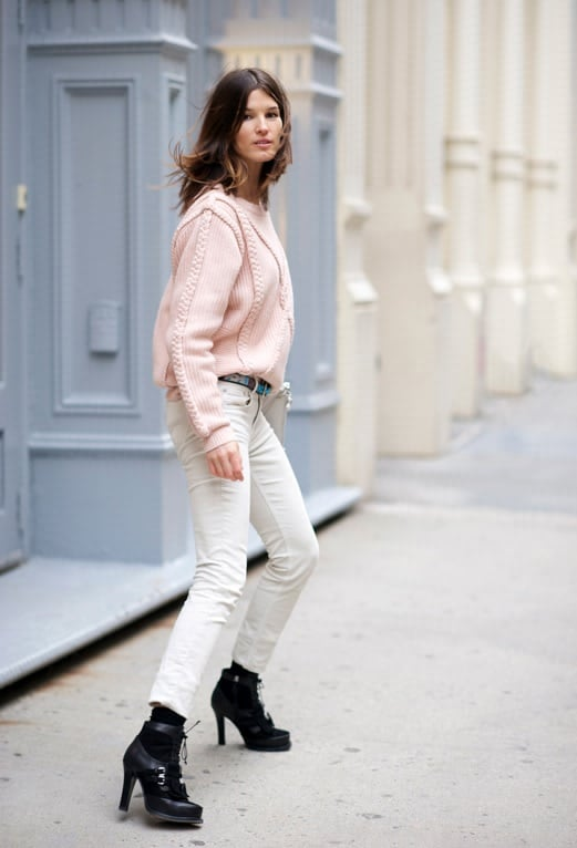 Chunky pale pink sweater with white pants and black booties