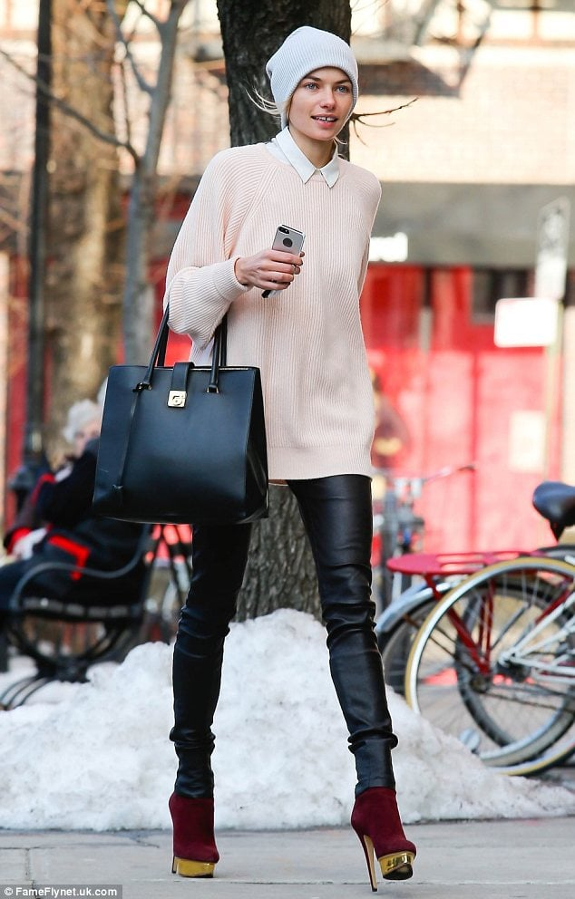Pale pink jumper and black leather pants with red platform heels