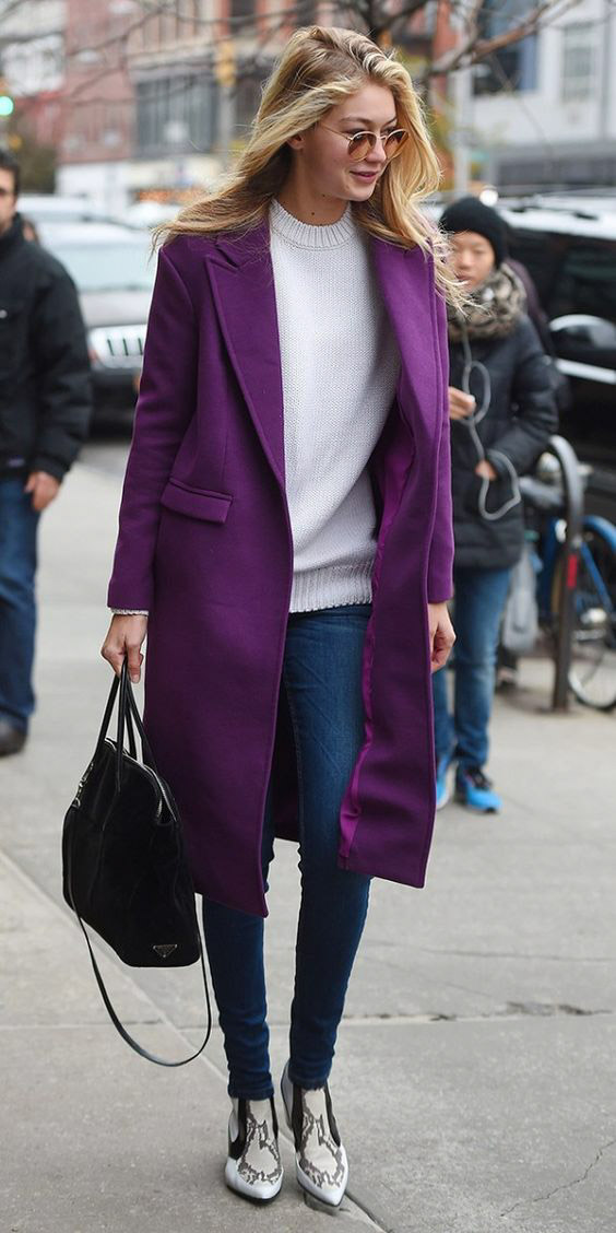 Chic in a long purple coat, cream seater, and snake-print boots